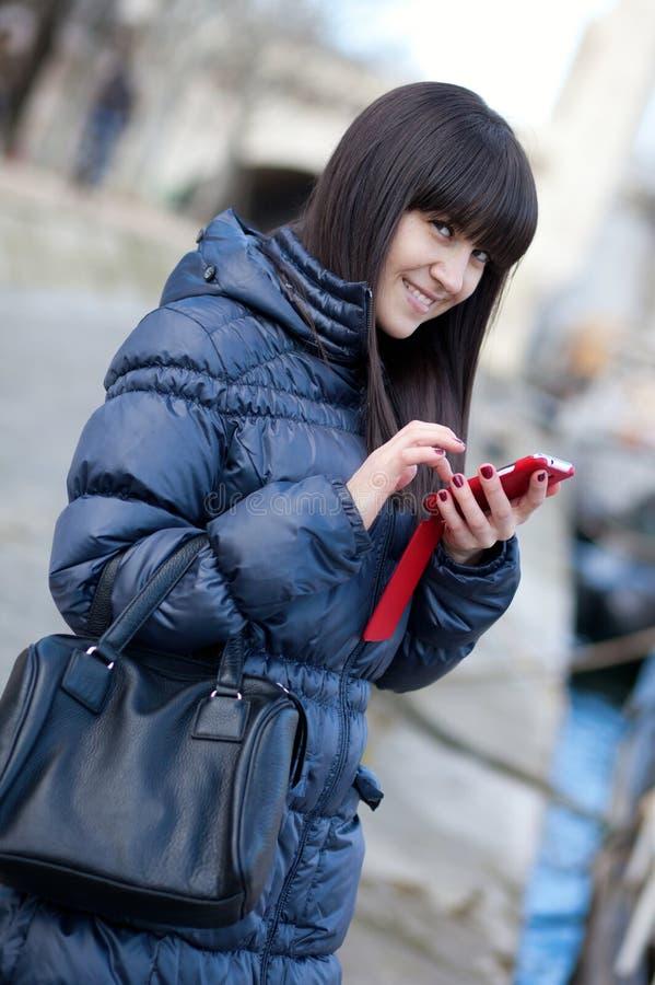 Invio felice della ragazza del brunette sms ad alcuno immagine stock