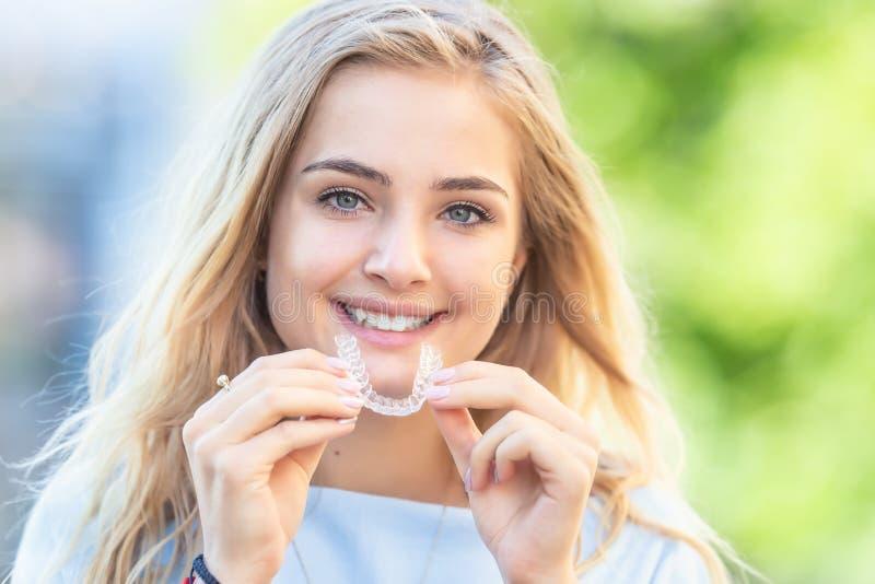 Invisalign orthodontics concept - Young attractive women holding - gebruikmakend van onzichtbare steunen of trainer stock afbeeldingen