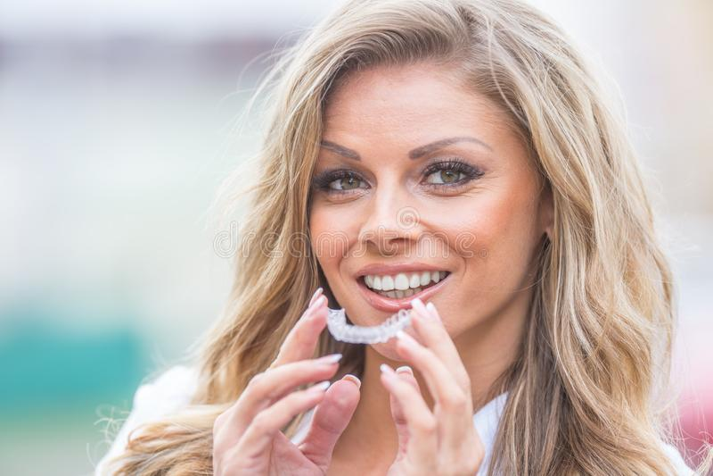 Invisalign orthodontics concept - Young attractive women holding - gebruikmakend van onzichtbare steunen of trainer royalty-vrije stock foto's