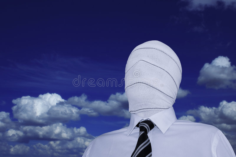 The invisible man. Man wearing a white shirt and a black and white striped tie with his face hidden under a bandage. + clipping path