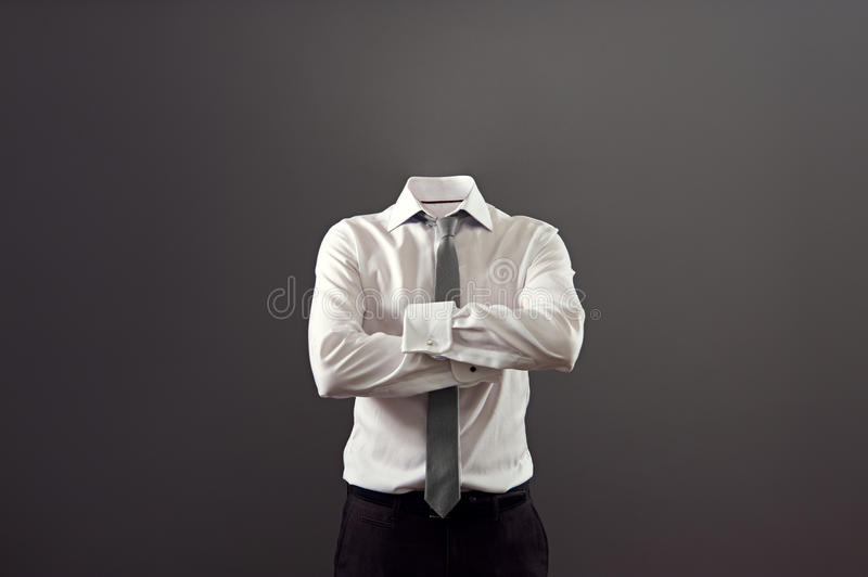 Invisible man standing with folded arms. Over his chest against grey background stock photo