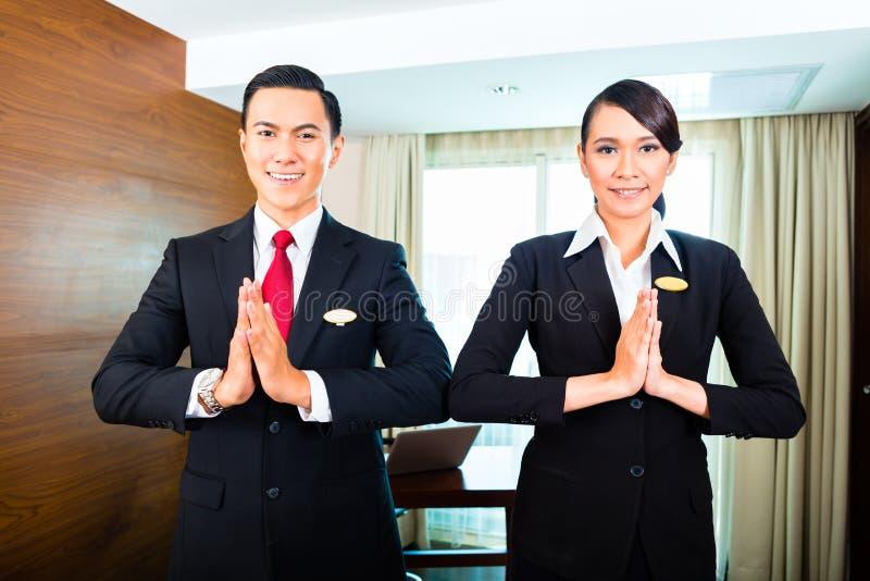 Invités de salutation de personnel dans l'hôtel asiatique image stock