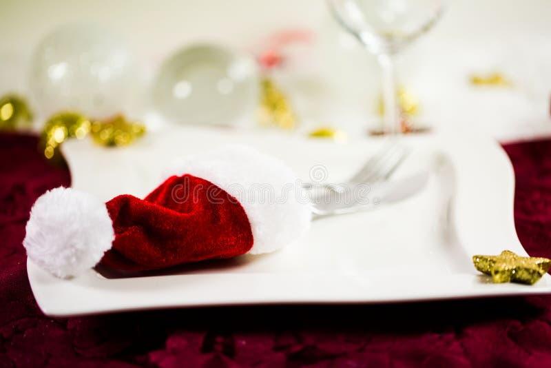 Invitación a comer, cena de la Navidad, sombrero de Santa Claus, placas, cubiertos, bolas de la Navidad fotos de archivo libres de regalías