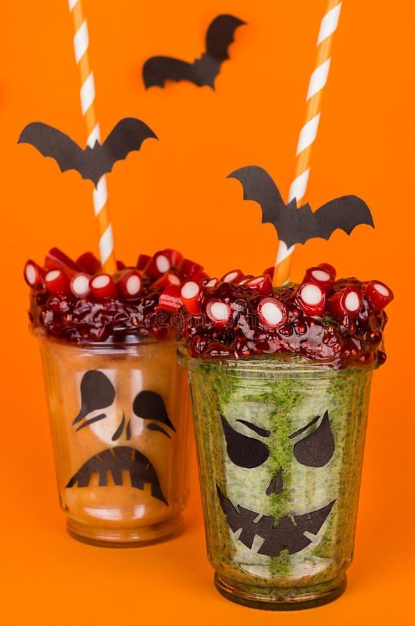 Invitación de Halloween, fondo anaranjado Postre verde con los palos, paja, caramelos del zombi de la diversión imagen de archivo
