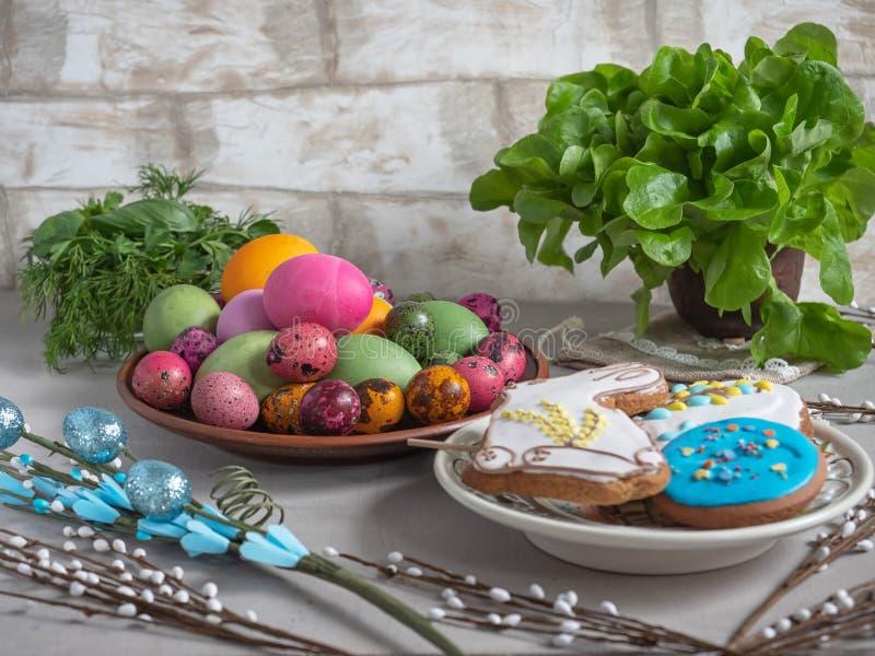 Invitación de Pascua de huevos coloreados, del pan de jengibre pintado, de hierbas frescas, y de ramitas del sauce imagen de archivo libre de regalías