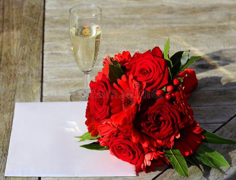 Invitación y flores de la boda foto de archivo