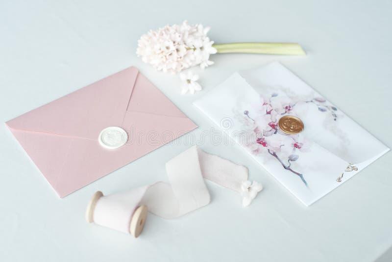 Invitaci?n de la boda como letra adornada en un mantel blanco con un centro de flores fotos de archivo