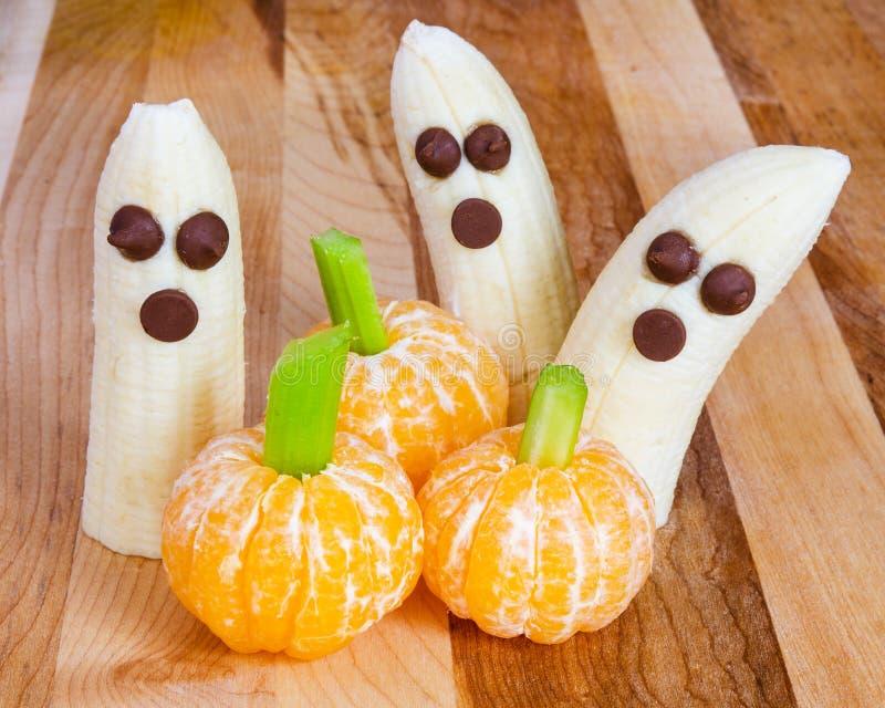 Invitaciones amistosas del niño de Halloween con los plátanos y las clementinas fotografía de archivo