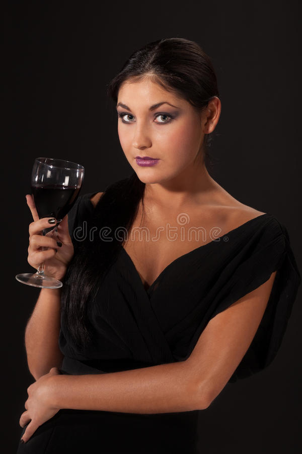 Invitation for a glass of wine. Charming lady inviting for a glass of wine royalty free stock photo