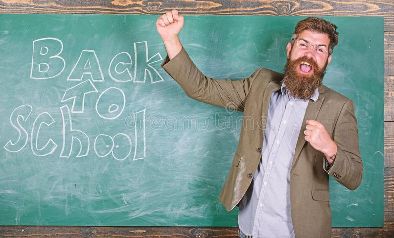 Invitation to celebrate knowledge day. Teacher or educator welcomes students while stands near chalkboard with. Inscription back to school. Teacher begin first royalty free stock photography