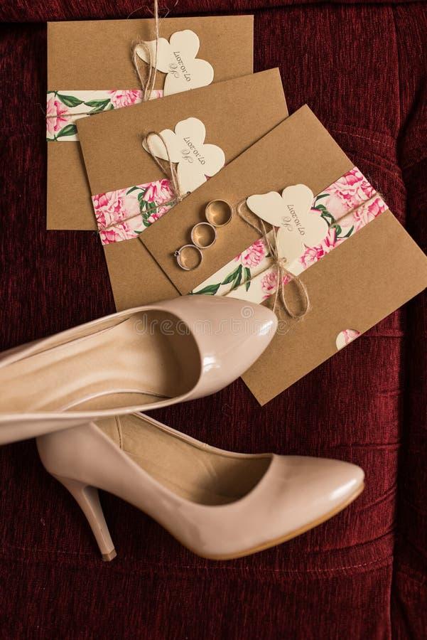 Invitations de mariage dans les enveloppes de métier, anneaux d'or et chaussures nuptiales beiges se trouvant sur un fauteuil rou photo libre de droits