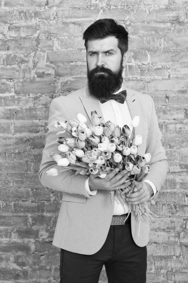 Invite her dating. Romantic man with flowers. Romantic gift. Macho getting ready romantic date. Waiting for darling. Tulips for sweetheart. Man well groomed stock photos