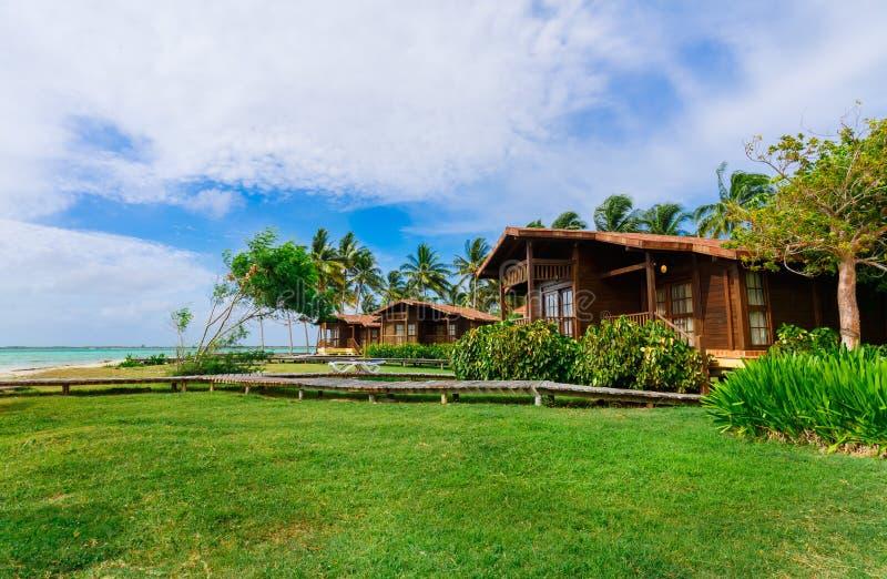 Invitera som är ursnyggt och att bedöva sikt av hotelljordning med bungalowslags tvåsittssoffa, bekväma hus som står nära strande royaltyfria foton