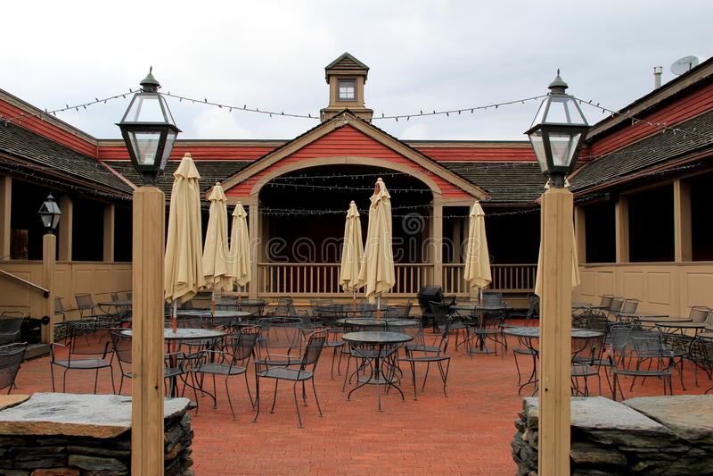Inviterande inställning av tabeller och stolar i borggården, lager för Yankeestearinljusflaggskepp, Deerfield mass, 2014 royaltyfria foton