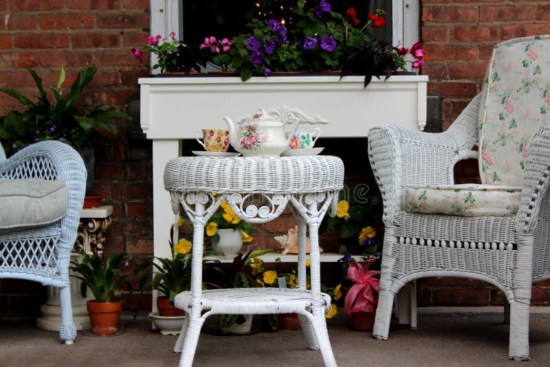 Inviterande vide- stolar, blommor och teservis på tabellen på en lägenhet, Oneida Community Mansion House, Oneida, New York, 2018 arkivbild