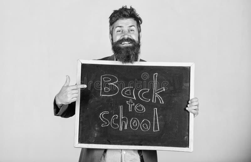 Inviti per celebrare il giorno di conoscenza L'uomo barbuto dell'insegnante sta e tiene la lavagna con l'iscrizione di nuovo alla fotografia stock libera da diritti