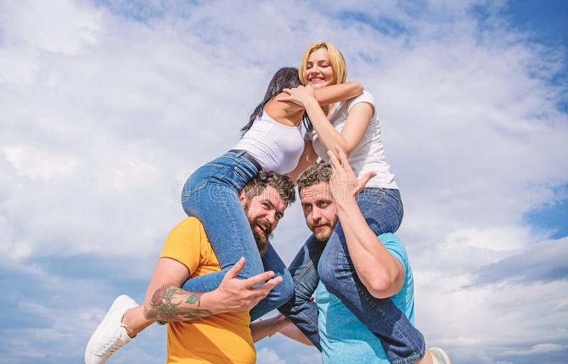 Inviting another couple to join. Friendship of families. Twice fun on double date. Couples in love having fun. Men carry. Girlfriends on shoulders. Summer stock image