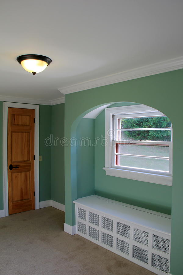 Inviting architectural design of homes interior. Inviting color and design of home's interior, with open space and window seat tucked under arched opening of royalty free stock photography