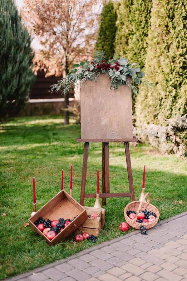 Inviting banner with autumnal composition of apples and grape. Inviting banner on easel with autumnal composition of red apples and dark blue grape in wooden box stock photo