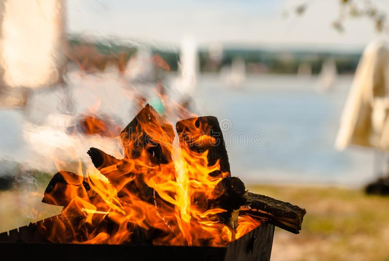 Inviting bonfire on the beach of the reservoir with yachts, people during the summer, bring back memories stock photo