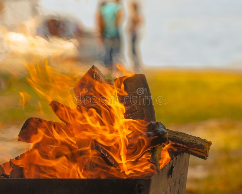 Inviting bonfire on the beach of the reservoir with yachts, people during the summer, bring back memories stock images