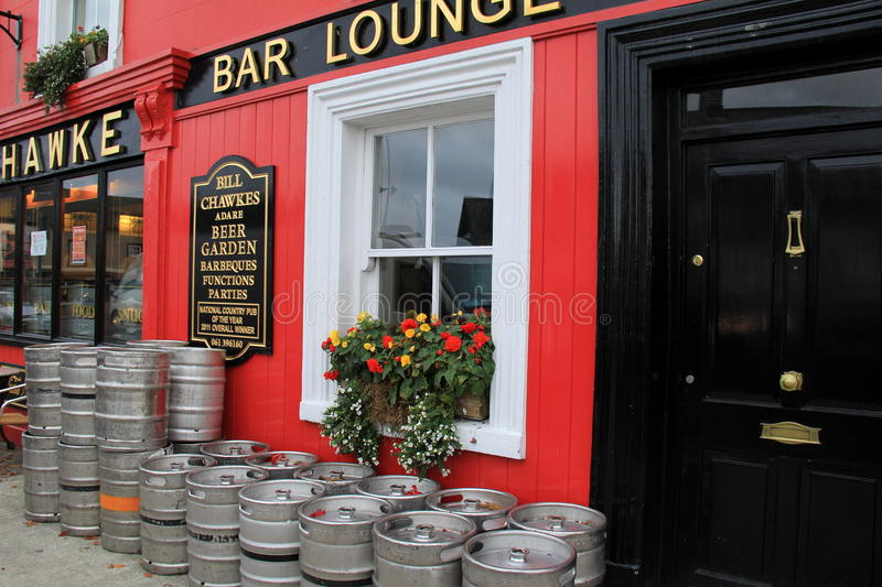 Inviting scene of colorful kegs and flowers in window boxes outside Bill Hawke Beer garden,Adare,Ireland,2014. Inviting scene with colorful flowers in window stock image
