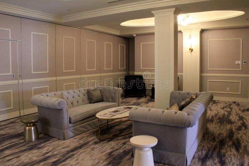 Welcoming gray couches with patterned rugs and painted walls in sitting area, The Adelphi Hotel, Saratoga Springs, New York, 2018. Inviting scene with royalty free stock photos