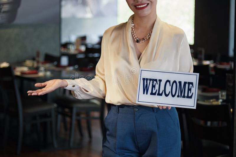 Inviting to restaurant. Cropped image of smiling woman inviting you to her restaurant stock photography