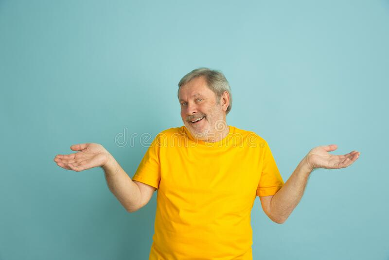 Caucasian senior man`s portrait isolated on blue studio background stock photo