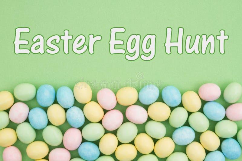 Invito felice di caccia dell'uovo con l'uovo di Pasqua della caramella fotografia stock