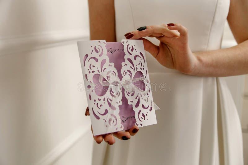 Invito lilla di nozze nelle mani della sposa immagine stock libera da diritti