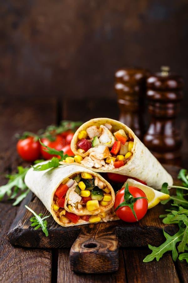 Involucri dei Burritos con carne di pollo e le verdure su fondo di legno immagine stock libera da diritti