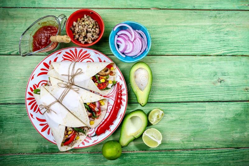Involucri dei Burritos con manzo, i funghi, tritato e verdure su un fondo di legno Burrito di manzo, alimento messicano Alimento  fotografie stock