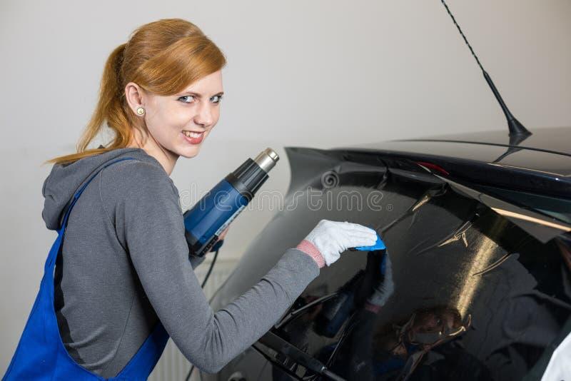 Involucro dell'automobile che tinge la finestra di automobile in garage con una stagnola o un film tinta fotografie stock