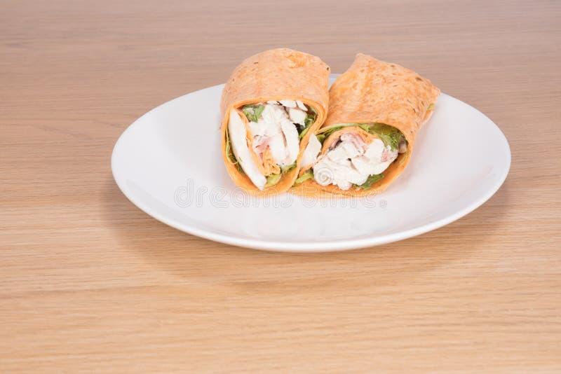 Involucro sano dell'insalata di pollo affettato a metà sul piatto fotografie stock