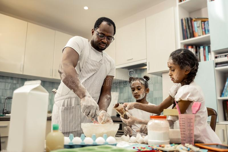 Two helpful funny daughters feeling involved in cooking with father. Involved in cooking. Two helpful funny daughters feeling extremely involved in cooking with stock photo