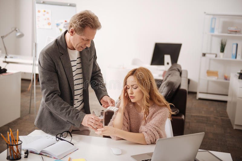 Involved mature manager taking care of sick woman in the office royalty free stock photos