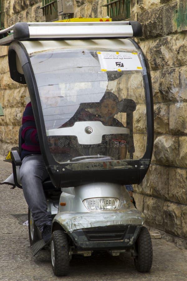 Inwalidzka hulajnoga negocjuje swój sposób przez wąskiej ulicy zdjęcia stock