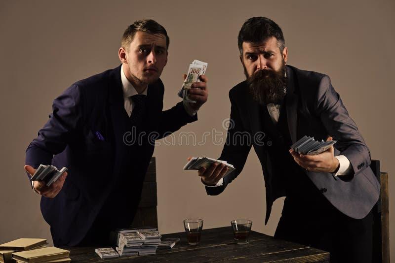 inwestycja pomyślna Potajemnie transakcja z gotówką Firma angażująca w bezprawnym biznesie Mężczyzna przy stołem z stosami fotografia royalty free