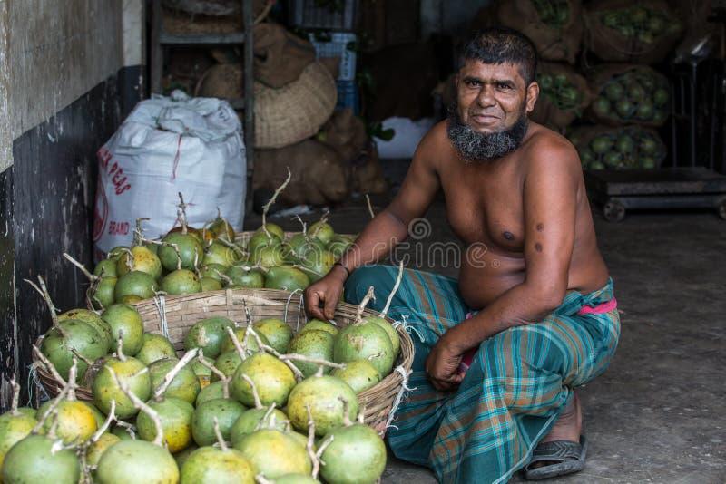 Inwoner van Bangladesh Bael-verkoper die hij op klanten bij een groothandelsmarkt in karwan Bazar in Dhaka, Bangladesh heeft gewa royalty-vrije stock afbeelding
