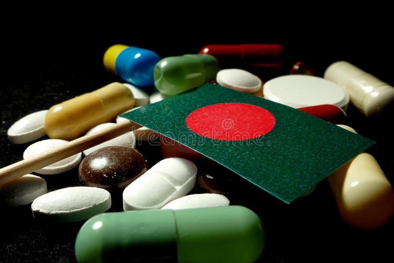 Inwoner van Bangladesh vlag met partij van medische die pillen op zwarte bac wordt geïsoleerd stock foto