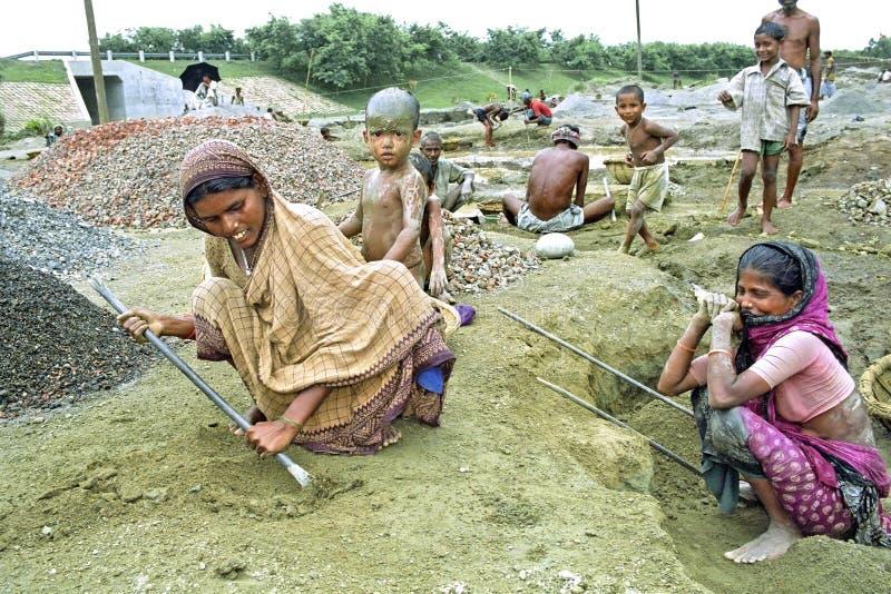Inwoner van Bangladesh vrouwen die met jonge geitjes in grintkuil werken stock fotografie
