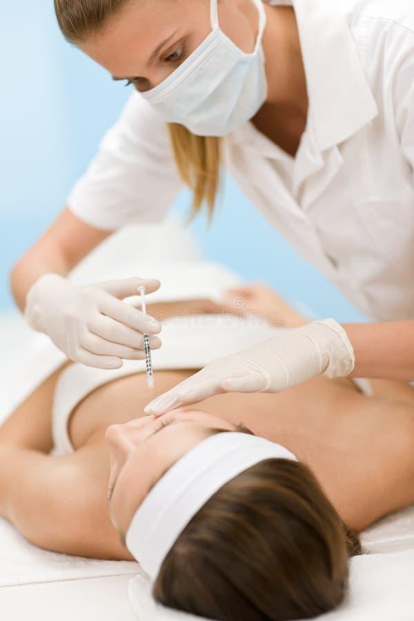 Inyección de Botox - mujer en el tratamiento cosmético imagen de archivo