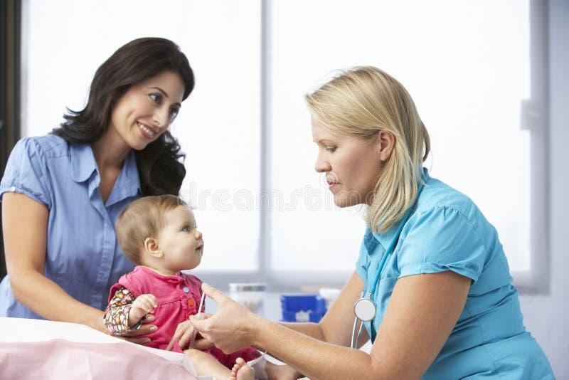 Inyección del bebé del doctor In Surgery Giving imagenes de archivo