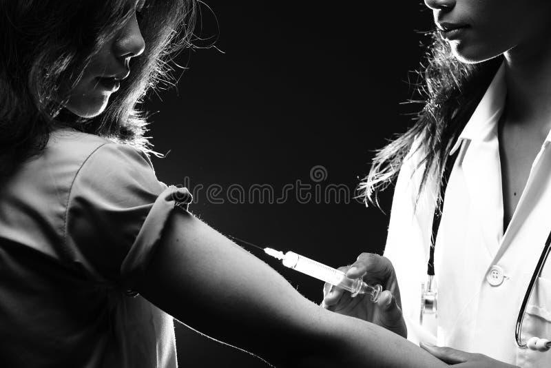 Inyecte la jeringuilla de la vitamina al paciente para tratar al enfermo de la curación imagenes de archivo