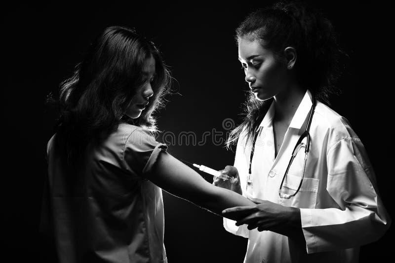 Inyecte la jeringuilla de la vitamina al paciente para tratar al enfermo de la curación fotografía de archivo libre de regalías
