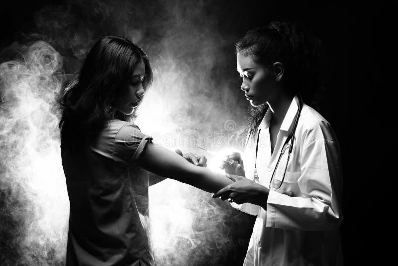 Inyecte la jeringuilla de la vitamina al paciente para tratar al enfermo de la curación imagen de archivo