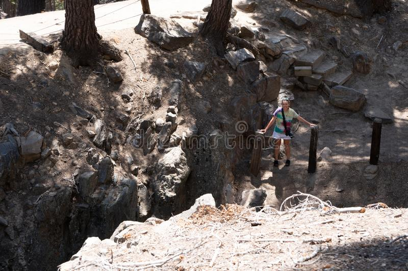 The Inyo Earthquake Fault in Mammoth Lakes California, female explores the area, showing the scale of the fault line. On a sunny summer day stock image