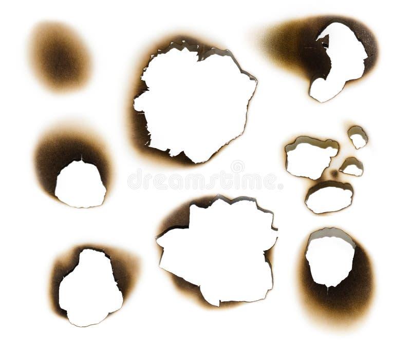 Inzameling van gebrande gaten in een stuk van document stock fotografie