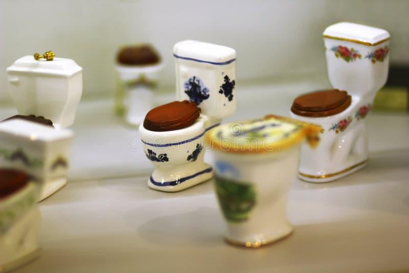 Inzameling van klassieke ceramische toiletkommen met houten zeteldekking, herinneringen op vertoning royalty-vrije stock foto